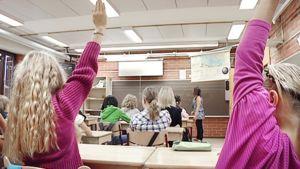 Oppilaat viittaavat oppitunnilla luokkahuoneessa.