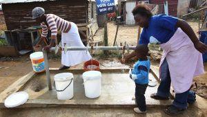 Paikalliset asukkaat noutavat vettä yleiseltä vesipisteeltä.