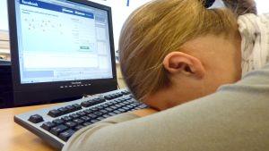Nainen pitää päätään työpöytäänsä vasten. Taustalla tietokone auki.