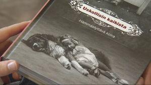 Kirjan kansi, jossa koira makaa tytön kanssa lattialla.