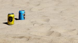 Kuvassa hiekkarannalle jätettyjä juomatölkkejä.