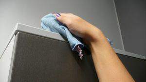 Kaapin päältä pyyhitään pölyjä sinisellä liinalla.