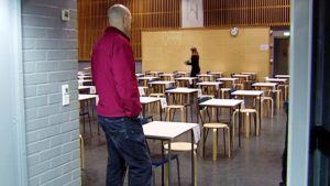 Ylioppilaskokeen valvoja tarkkailee salia.
