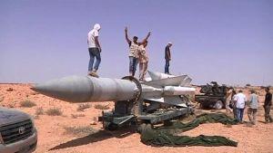 Libyan kapinallisia seisomassa Gaddafin joukkojen hylkäämän ohjuksen päällä Bani Walidiin johtavan tien varrella torstaina.