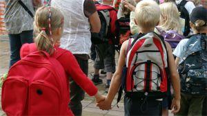 Kaksi koululaista pitää toisiaan kädestä kiinni