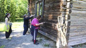 Kaksi naista tilkitsee hirsiseinää riveellä ja kolmas seuraa työskentelyä.