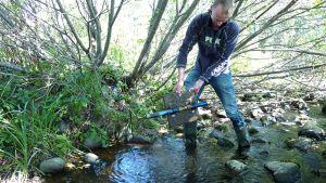 Mies esitelee purossa olevaa vedenlaatua mittaavaa laitetta