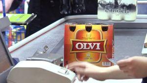 Olutta kaupan kassahihnalla.
