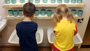 Kaksi lasta pesee käsiään päiväkodissa.