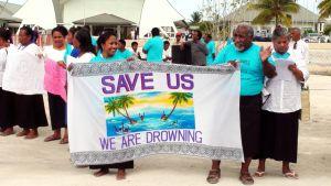 Kiribatin paikallisasukkaita lakanan kanssa. Lakanassa lukee Save us, we are drowning.