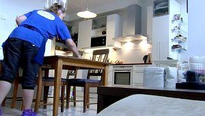 Siivousalalla pelätään työpaikkojen olevan vaarassa. Kuvassa siivousyrityksen työntekijä siivoaa olohuoneen pöytää.