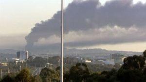 Kaupungin ylle kohoaa savu palavasta tehtaasta