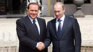 Silvio Berlusconi ja Vladimir Putin puristavat kättä.