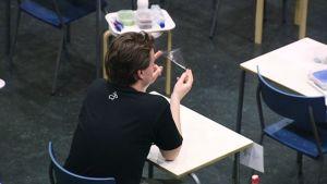 Ylioppilaskirjoitukset alkamassa koulun salissa, poika pyörittää kolmioviivainta käsissään.
