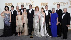 Mad Men -sarjan tuotantoryhmä poseeraa Emmy-pokaalin kanssa.