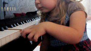 Pieni tyttö soittaa pianoa