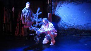 Kaksi miestä istuttaa näyttämöllä puuta.