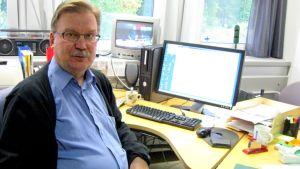 Sanomalehti Karjalaisen eläkkeelle jäävä uutispäällikkö Jouko Salmela istuu työhuoneessaan.