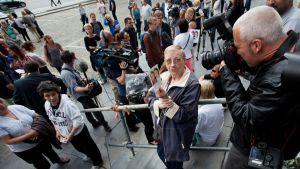 Mielenosoittajajoukko ja lehtikuvaajia oikeustalon portailla.