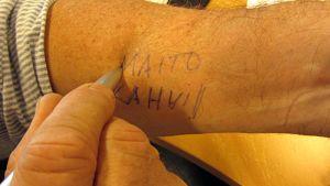 Kuvassa mies kirjoittaa muistivinkkiä käteensä