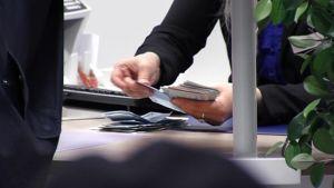 Pankkivirkailija laskee rahoja pankin tiskillä.