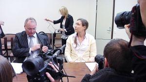 Anneli Auer istuu kuvaajien ympäröimänä oikeussalissa.