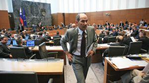 Janez Jansa papereita kädessä kävelemässä pois parlamenttisalista.