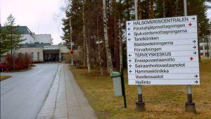 Kuvassa Malmin alueen opastaulu, taustalla sairaalan pääsisäänkäynti.