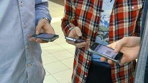Ihmisiä näppäilemässä kännyköitään.