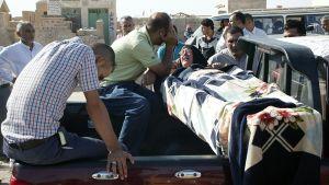 Ihmiset surevat pommi-iskussa surmansa saaneen uhrin arkun äärellä.