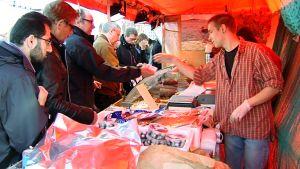 Ihmisiä silakkamarkkinoiden myyntikojulla.
