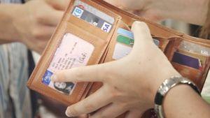 Asiakas lompakko kädessään kaupan kassalla.