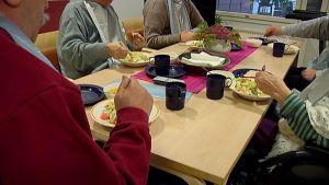 Palvelukodin asukkaita syömässä.