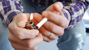 Mies sytyttää tupakkaa.