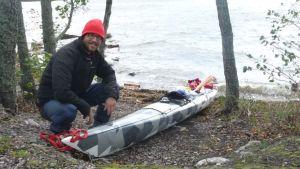 Erik Lerouge kyykyssä meren äärellä kajakkinsa vieressä.