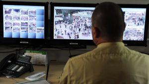 Poliisi katselee tietokoneruutuja, joilla näkyy valvontakamerakuvaa.