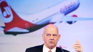 Joachim Hunold puhuu tiedotustilaisuudessa, taustalle heijastettu lentokoneen kuva.