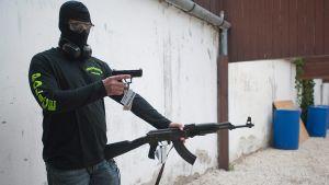 Unkarin terrorisminvastaisen yksikön jäsen esittelee kuvaajille takavarikoituja aseita.