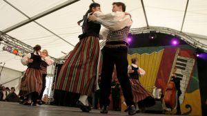 Nuoria tyttöjä ja poikia tanssimassa kansantansseja kansallispuvut päällä