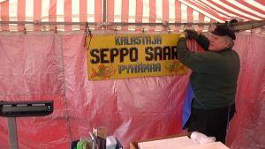 Kalastaja Seppo Saari rakensi myyntitelttaansa keskiviikkona.