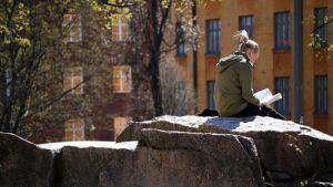 Nuori nainen lukee kirjaa kalliolla.