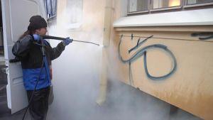 Juha Skog puhdistaa paineilmalla talon seinää töhrystä.