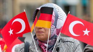 Turkinsaksalainen nainen hieluttaa kahta Turkin ja yhtä Saksan pienoislippua.