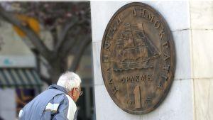 Mies tutkii Ateenan keskustassa sijaitsevaa monuimenttia, jossa yhden drakman kolikon suuri pronssinen kopio