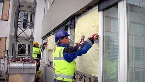Työmiehiä asentamassa eristyslevyä kerrostalon seinään