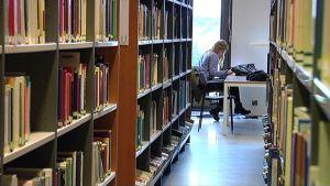 Opiskelija kirjastossa.