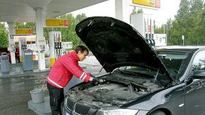 Huoltoaseman henkilökuntaan kuuluva mies huoltamassa autoa.