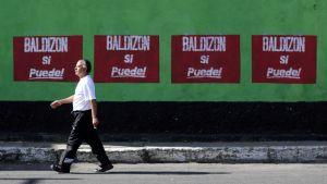 Mies kävelee presidenttiehdokas Baldizonin vaalijulisteiden edessä Guatemala Cityssä.