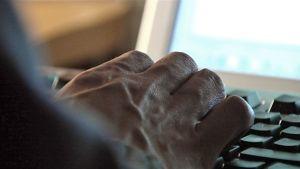 Miehen käsi tietokoneen näppäimistöllä.