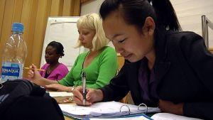 Maahanmuuttajat opiskelemassa.